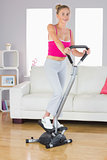 Sporty smiling blonde training on step machine