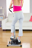 Rear view of sporty woman training on step machine