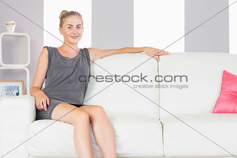 Casual smiling blonde relaxing on couch