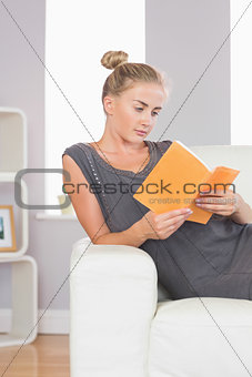 Casual calm blonde relaxing on couch reading a book