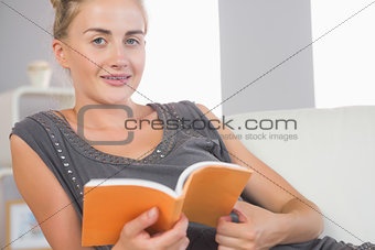 Casual happy blonde relaxing on couch reading a book
