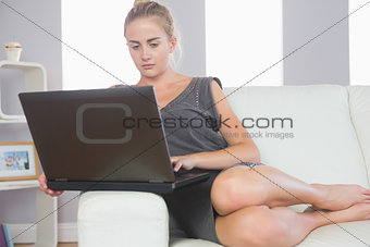 Casual stern blonde relaxing on couch using laptop