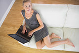 Casual smiling blonde relaxing on couch using laptop