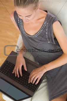 Casual blonde relaxing on couch on typing laptop