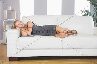 Casual peaceful blonde lying on couch sleeping
