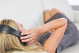 Casual attractive blonde lying on couch listening to music