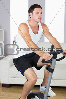Attractive sporty man exercising on bike