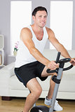 Smiling sporty man exercising on bike