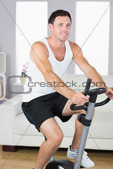 Smiling sporty man exercising on bike
