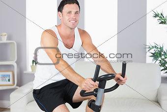 Cheerful sporty man exercising on bike