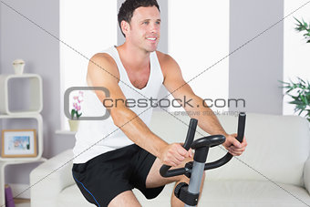 Content sporty man exercising on bike