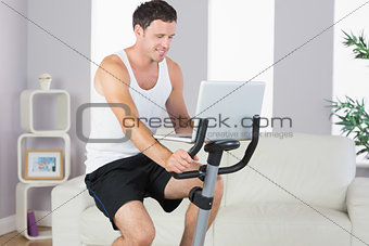 Content sporty man exercising on bike and using laptop