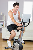 Happy sporty man exercising on bike and using laptop