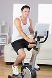 Smiling sporty man exercising on bike and holding laptop