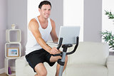 Cheerful sporty man exercising on bike and holding laptop