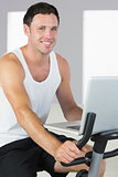 Attractive sporty man exercising on bike and holding laptop