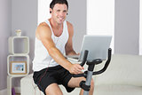Sporty smiling man with earphones exercising on bike and holding laptop