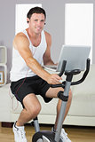 Sporty content man with earphones exercising on bike and holding laptop
