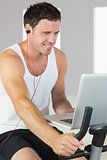 Sporty attractive man with earphones exercising on bike looking at laptop