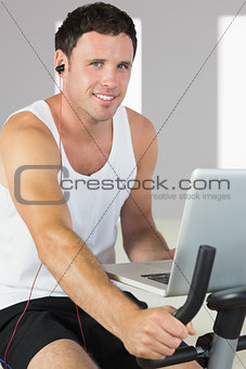 Sporty man with earphones exercising on bike, holding laptop and smiling