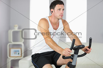 Attractive sporty man exercising on bike and listening to music