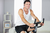 Smiling sporty man exercising on bike and listening to music