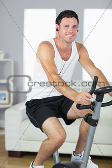Cheerful sporty man exercising on bike and listening to music