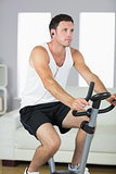 Handsome sporty man exercising on bike and listening to music