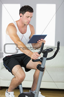 Handsome sporty man exercising on bike and using tablet