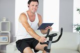 Smiling sporty man exercising on bike and holding tablet