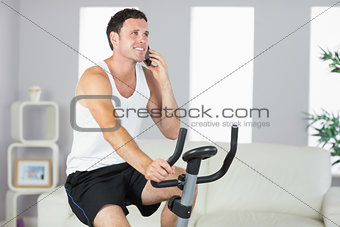 Smiling sporty man exercising on bike and phoning