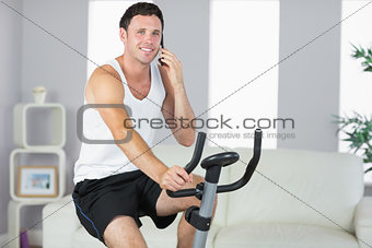Cheerful sporty man exercising on bike and phoning
