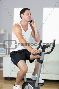 Handsome sporty man exercising on bike and phoning
