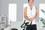 Smiling sporty man standing next to exercise bike