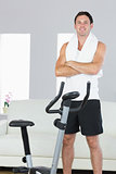 Smiling sporty man standing next to exercise bike cross armed