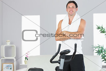 Cheerful sporty man standing next to exercise bike cross armed