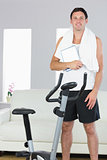 Cheerful sporty man standing behind exercise bike holding tablet