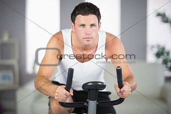 Attractive sporty man exercising on bike looking at camera