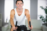 Attractive fit man exercising on bike smiling at camera