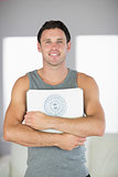 Sporty cheerful man holding a scale