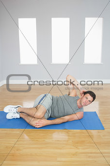 Attractive sporty man doing abdominal crunch looking at camera