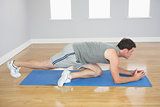 Attractive sporty man exercising on blue mat