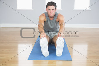 Attractive sporty man stretching his legs