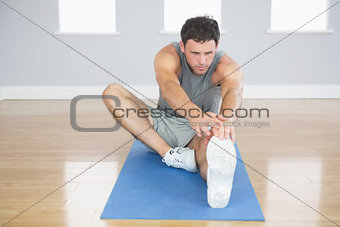 Attractive sporty man stretching his right leg