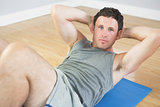 Calm sporty man doing sit ups on blue mat