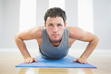 Handsome sporty man doing push ups on blue mat