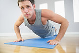 Attractive sporty man doing push ups on blue mat looking at camera