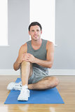 Cheerful sporty man sitting on blue mat