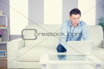 Attractive casual man using laptop