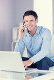 Cheerful casual man using laptop and phoning